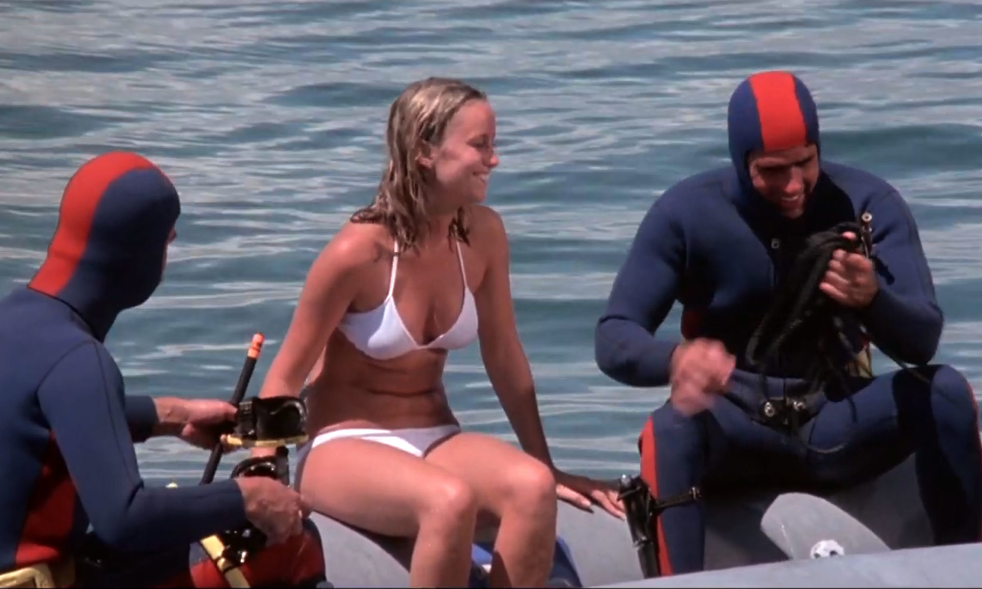 Susan George in a bikini flanked by two dudes in wetsuits