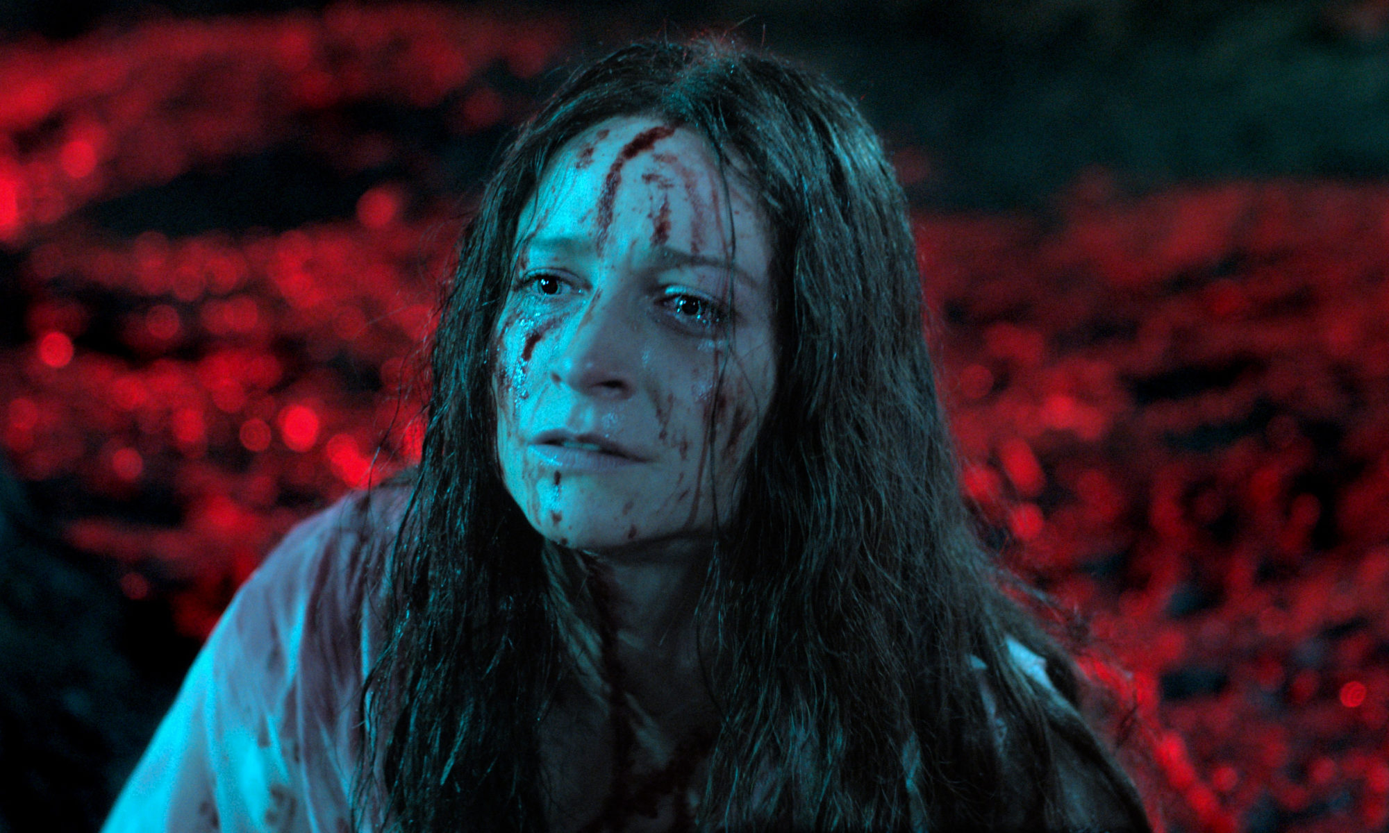 A woman in a forest with a red background and streaks of blood drying on her face